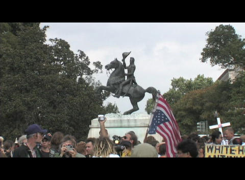 Medium-shot of a groups of anti-Iraq-war protestors in front of a Washington, DC statue Footage