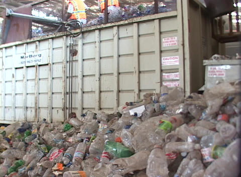 Workers prepare large piles of discarded plastic bottles at a recycling center Footage