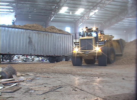 A loader moves piles of recyclable materials in a recycling center Footage