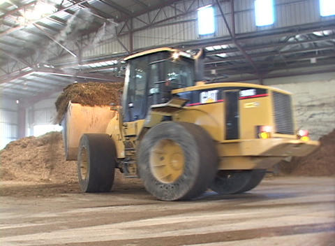 A bulldozer scoops debris into a large container truck in... Stock Video Footage