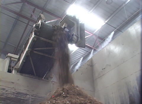 Dirt and other waste pours off a conveyor belt at a recycling center Footage