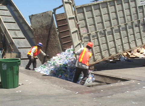 Workers unload thousands of plastic bottles at a recycling center Footage