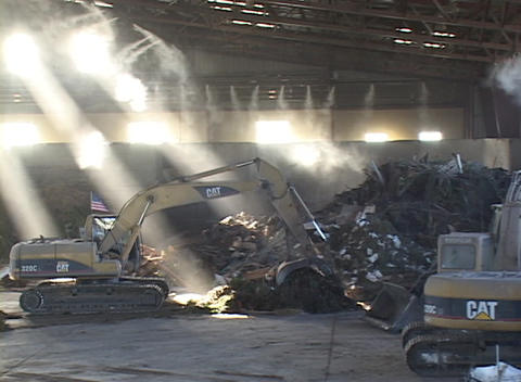 A shovel scoops material at a recycling center Stock Video Footage