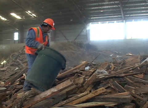 A recycling plant worker places scraps into a garbage can Stock Video Footage