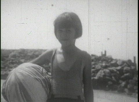 People play and frolic on the beach in this 1940's home... Stock Video Footage