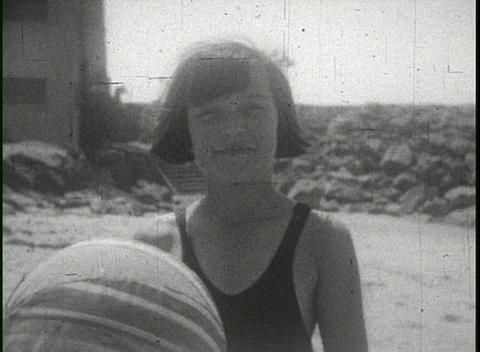 People play and frolic on the beach in this 1940's home movie clip Footage