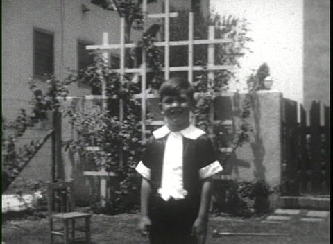 Home movie shots of a family in front of a house includes a crying child Footage