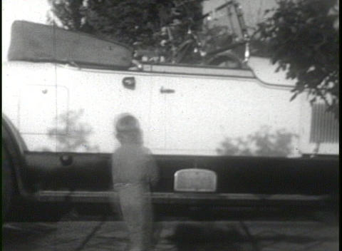 A boy gets behind the wheel of a 1920's automobile and... Stock Video Footage
