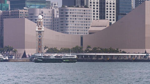 Ferry transiting in front of the Tsim Sha Tsui clock tower. UltraHD footage Footage