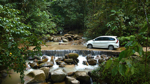 Car crossing cement bridge as river flows over road in Borneo. Malaysia Footage