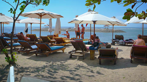Tourists relaxing on a private resort's beach in Sanur. Bali. Indonesia Footage