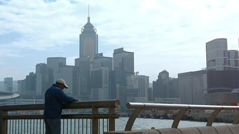 Hong Kong man fishing from an urban bridge. 4k 2160p footage Footage