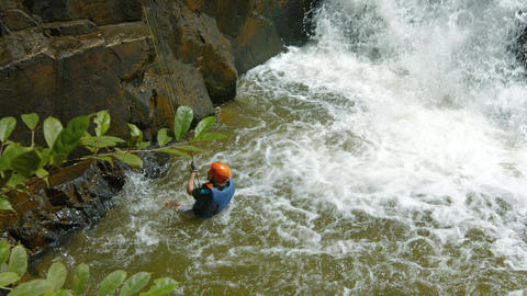 Adventurous tourist rappels into the river beneath Datanla Falls near Da Lat Footage