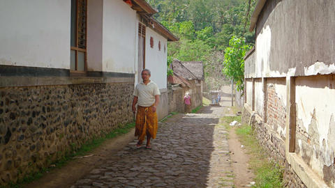 Locals walking along a typical. old street in a Balinese village Footage