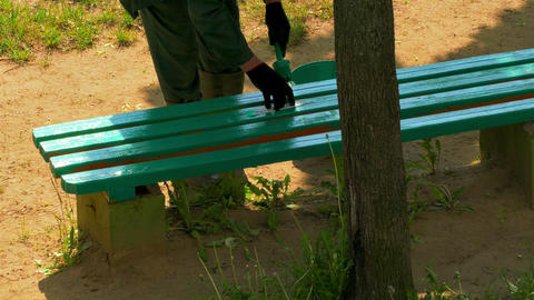 4K Worker Paints Wooden Bench With Green Paint and Then Sticks Piece Of Footage