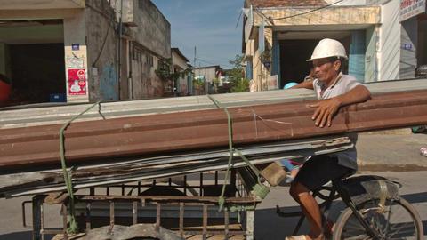 Closeup Man Carries Long Pipes on Bike along Street in Vietnam Footage