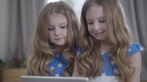 Close-up of two pretty Caucasian twin sisters with long wavy hair using tablet Live Action