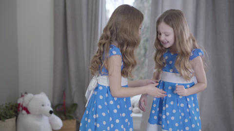 Side view of two identical sisters having fun at home. Joyful Caucasian twins in Live Action