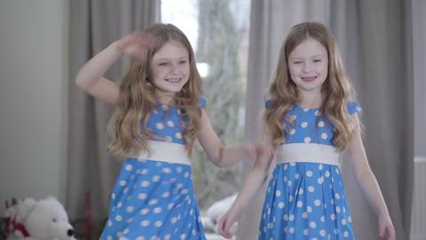 Middle shot of joyful twin sisters having fun indoors. Joyful brunette Caucasian Live Action