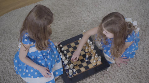 Top view of two brunette Caucasian twin sisters playing chess indoors. Little Live Action