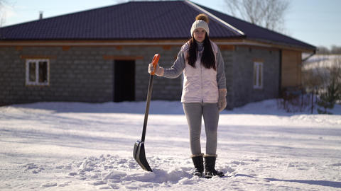 young girl stands with a shovel in the backyard. woman ready to clear snow after Live Action