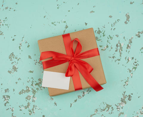 square box wrapped in brown kraft paper and tied with a red silk Fotografía