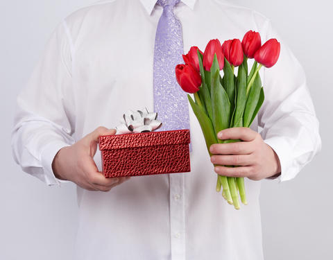 man in a white shirt and a lilac tie holding a bouquet of red tu Fotografía