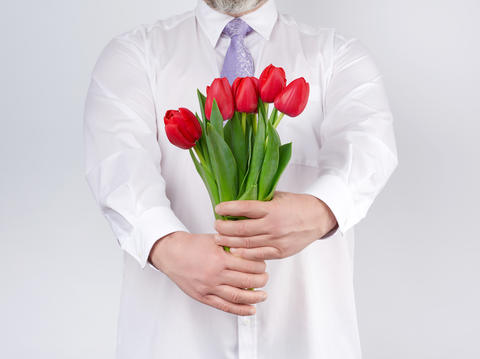 adult man in a white shirt and a lilac tie holding a bouquet of Fotografía
