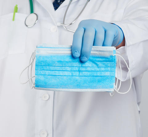 doctor in a white coat, blue latex sterile gloves holds textile Fotografía