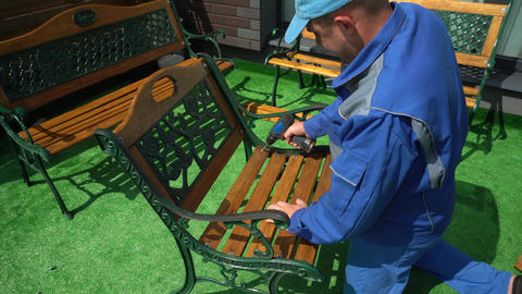 Man with electric screwdriver repairing outdoor furniture chair in house yard Live Action