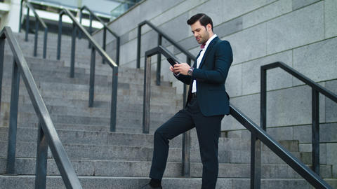 Businessman laughing with phone in hand at street. Man using smartphone outdoor Live Action