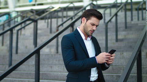 Closeup man typing on phone outdoor at stairs. Man using mobile phone outside Live Action