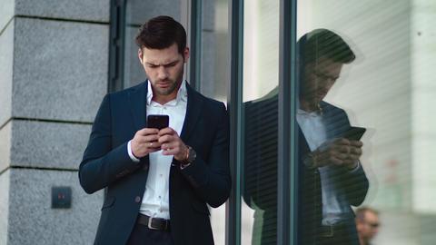 Closeup businessman standing near building. Businessman using smartphone outside Live Action
