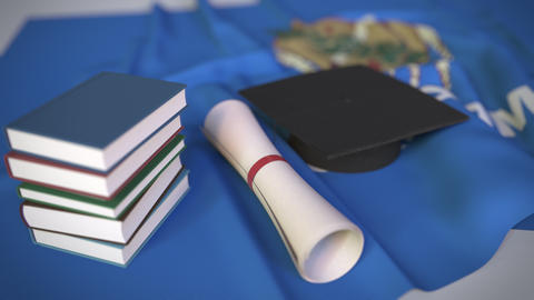 Graduation cap, books and diploma on the flag of Oklahoma. Higher education in Live Action