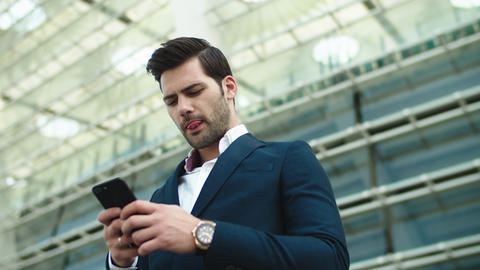 Portrait businessman using smartphone. Man standing with phone in hand outdoors Live Action