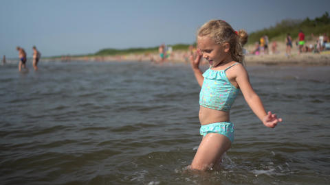 Active playful little girl dance wading through sea water waves. Funny child Live Action