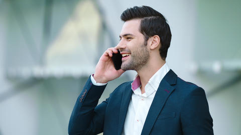 Portrait businessman using smartphone. Man smiling with phone in hand outdoors Live Action