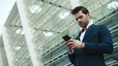 Portrait businessman looking away. Businessman using smartphone outdoors Live Action