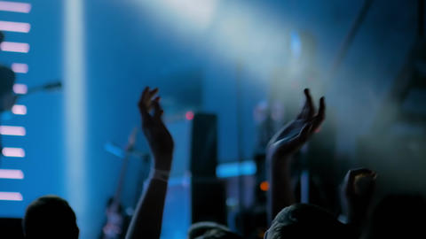 Man silhouette partying and clapping at rock concert with blue stage lighting Live Action
