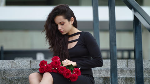 Closeup woman sitting with roses. Woman touching bouquet of roses on stairs Live Action