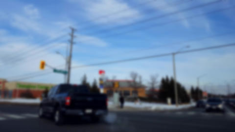 Turning Left at City Light Intersection With Blur Effect. Turn in Urban Intersection With Traffic in Live Action