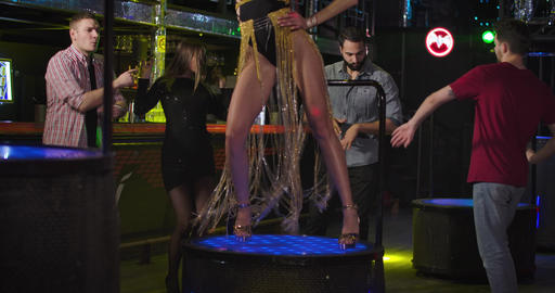 Long legs of seductive Caucasian PJ dancing on stage as night club visitors Live Action