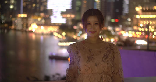 Asian Chinese girl in happy mood smiling for the camera in urban city background which is fully Live Action