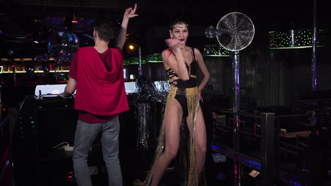 Long shot of young seductive go go dancer and male DJ dancing on stage. Handsome Live Action