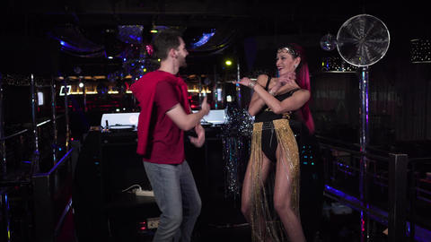 Young cheerful man and woman dancing on stage in night club. Smiling male DJ and Live Action