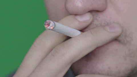 Cigarette in the mouth of a smoker. Close-up. Slow motion. Chroma Key. Green Live Action