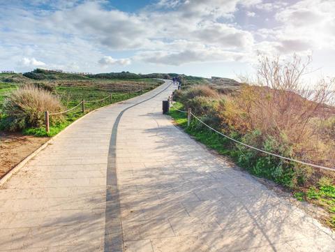 Stony tilled paved footpath at sea, dark stripe Photo