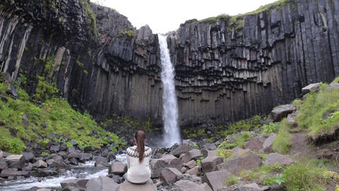 Woman enjoying majestic Svartifoss waterfall in Skaftafell on Iceland Live Action
