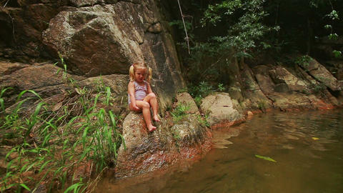 Closeup Little Blond Girl Sits on Stone Bank Eats Fruit Footage