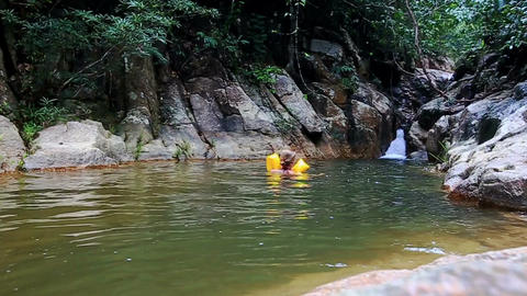 Mother Little Girl in Arm-bands Swim in Pond by Waterfall Footage